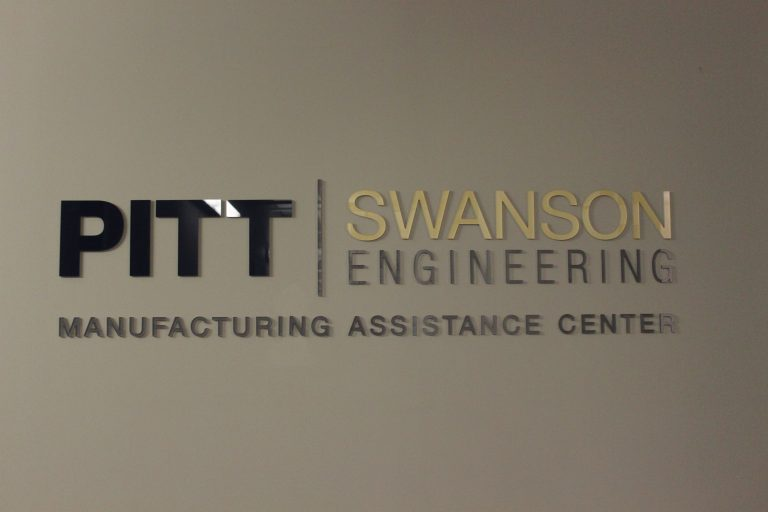 wall with Pitt Swanson Engineering Manufacturing Assistance Center logo